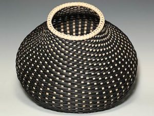 Photo of Billie Ruth Sudduth's Contemporary Cat's Head Basket in Black and Walnut tilted to show the interior of the basket